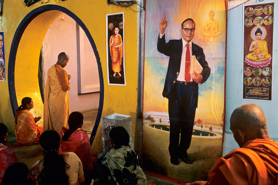 Dalit Buddhist worship in front of a banner of Dr. B.R. Ambedkar a main architect of the Indian Constitution promoter of Buddhism amongst the Dalits.